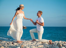 Young man proposing marriage to happy young woman Stock Photos