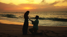 Young Man Proposing To Woman Sunset-Lit Beach. Young man gets on one knee and puts ring on womans finger on sunset-lit beach Oahu Hawaii