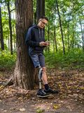 Young man with prosthetic leg using his smartphone. Young man with prosthetic leg leans against a tree in a park looking into his smartphone royalty free stock photography