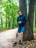 Young man with prosthetic leg using his smartphone. Young man with prosthetic leg leans against a tree in a park looking into his smartphone stock photography