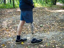 Young man with prosthetic leg walking. In a park in autumn stock photo