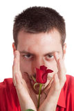 Young man protecting a red rose Royalty Free Stock Image