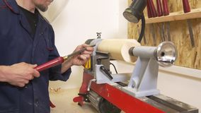 Young man in protective mask makes woodworking of joinery using hand screwdriver in workshop. Close up stock video footage
