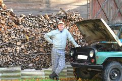 Young man proud of his old car. Smiling man standing close to his old jeep in front of woodshed Royalty Free Stock Image