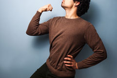 Young man in proud stance with fist raised Stock Photography