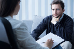 Young man at psychologist's office stock images