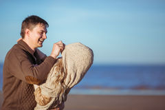 A young man is pulling her wifes poncho on her head Stock Photo