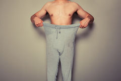 Young man pulling at his trousers Royalty Free Stock Photo