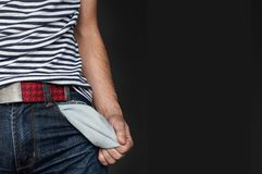Young man pulling out empty pocket. On black isolated background. A guy without money, with empty pockets. Left place for text Royalty Free Stock Image