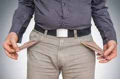 Man pulling out empty pockets - poor people concept. Young man pulling out empty pockets - poor people concept royalty free stock images