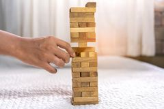 Young man pulling out wood block fail. On building tower at home and drape change, choice business risking dangerous project plan failure construction Royalty Free Stock Photography