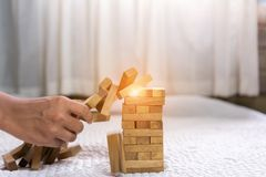 Young man pulling out wood block fail. On building tower at home and drape change, choice business risking dangerous project plan failure construction concept Stock Images