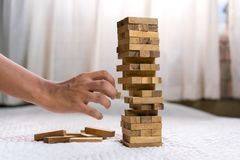 Young man pulling out wood block fail. On building tower at home and drape change, choice business risking dangerous project plan failure construction concept Royalty Free Stock Photo