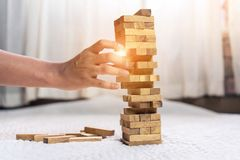 Young man pulling out wood block fail. On building tower at home and drape change, choice business risking dangerous project plan failure construction concept Stock Image