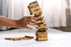 Young man pulling out wood block fail. On building tower at home and drape change, choice business risking dangerous project plan failure construction Stock Photography