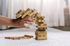 Young man pulling out wood block fail. On building tower at home and drape change, choice business risking dangerous project plan failure construction Royalty Free Stock Images