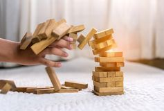 Young man pulling out wood block fail. On building tower at home and drape change, choice business risking dangerous project plan failure construction Stock Photo