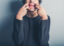 Young man pulling silly faces Stock Image