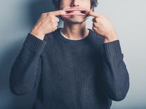 Young man pulling silly faces. A young man wearing a black sweater is pulling silly faces Royalty Free Stock Photography