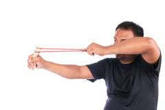 Young man pulling sling shot Stock Images