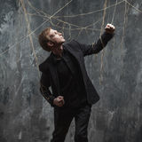 Young man pulling something behind him. Concept of manipulation and slavery. Young man in a black suit got caught in the web stock photography