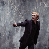 Young man pulling something behind him. Concept of manipulation and slavery. Young man in a black suit got caught in the web royalty free stock image