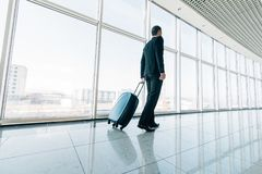Young business man pulling suitcase in modern airport terminal. Travelling guy or businessman concept. Business trip. Young man pulling suitcase in modern stock photo