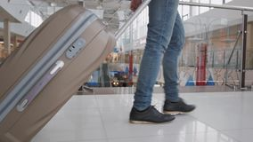 Young man pulling suitcase in modern airport terminal. Travelling guy wearing smart casual style clothes walking away. With his luggage while waiting for stock video