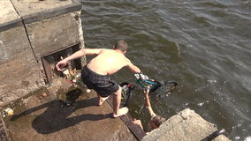 The young man pulls out a bike from the water. 4K. The young man pulls out a bike from the water. Shot in 4K ultra-high definition UHD, so you can easily crop stock video footage