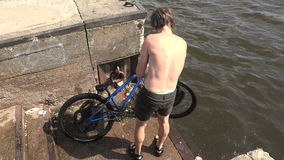 The young man pulls out a bike from the water. 4K. The young man pulls out a bike from the water. Shot in 4K ultra-high definition UHD, so you can easily crop stock video