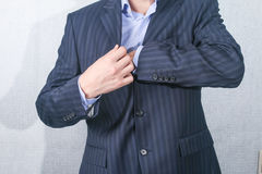 young man pulls something from his jacket pocket Royalty Free Stock Photos