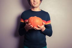 Young man with pumpkin Stock Photography