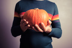 Young man with pumpkin Stock Images