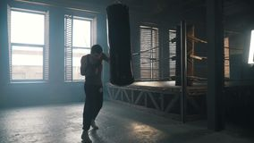 Young man punch the bag hard near boxing ring in industrial interior silhouette. Young man punch the bag hard near boxing ring in industrial interior with stock video