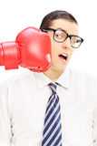 Young man punched by a red boxing glove Royalty Free Stock Photography