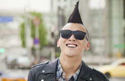 Young man with punk Mohawk and sunglasses smiling Royalty Free Stock Images