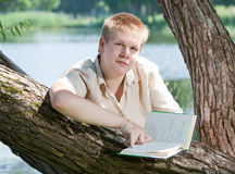 The young man reads the book on the river bank Stock Photos