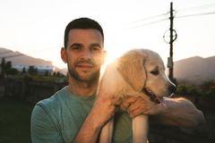 Young man with puppy dog in arms stock image