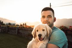 Young man with puppy dog in arms royalty free stock images