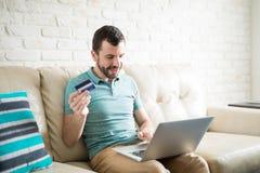 Latin man shopping online with credit card Stock Photos