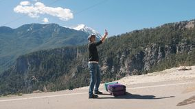 Young man with purple suitcase hitchhiking on sunny day. High in the mountains stock footage