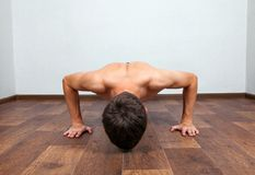 Young Man Push Up. On the Floor in the Room stock photo