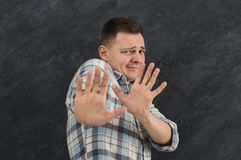 Young man expressing disgust, grimacing. Young man pushing away with his hands in foreground, expressing his refusal, aversion or repulsion with stopping hand Royalty Free Stock Image