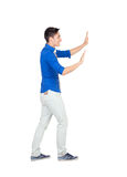 Young man pushing with blue shirt Royalty Free Stock Photography