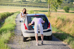 Young man pushing a car in a country road Royalty Free Stock Image