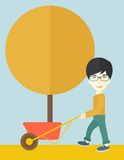 Young man pushing the cart with tree Stock Image