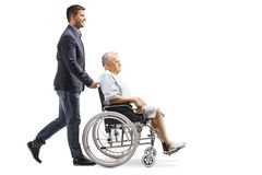 Young man pushing an elderly male patient in a wheelchair stock photos