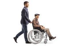 Young man pushing an elderly man in a wheelchair. Full length shot of a young men pushing an elderly men in a wheelchair isolated on white background royalty free stock photos