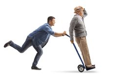 Young man pushing a hand truck with a mature man riding on it. Full length profile shot of a young men pushing a hand truck with a mature men riding on it Royalty Free Stock Images