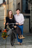 Young man pushing his girlfriend on the bicycle Stock Photography